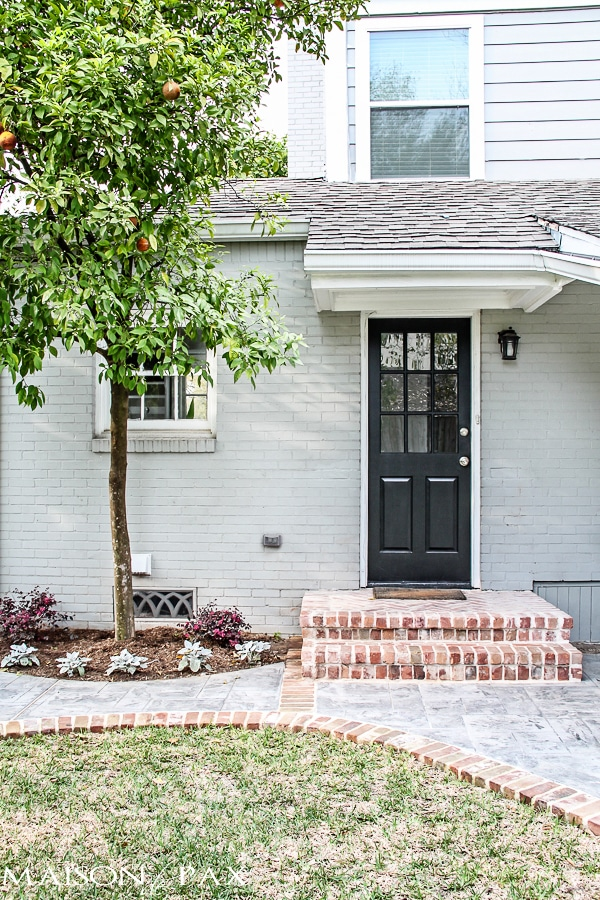gray house with brick steps and black door | maisondepax.com