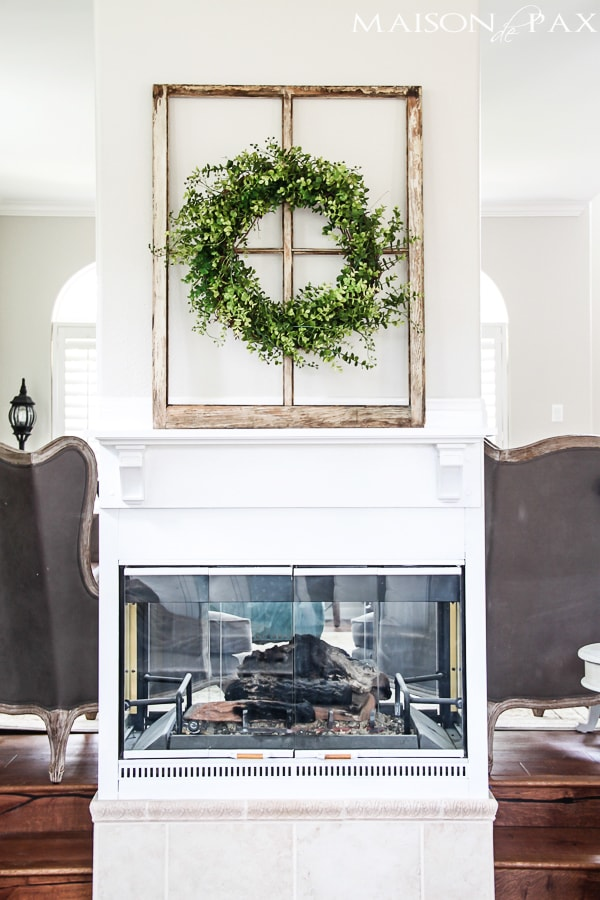I love this fireplace makeover! Some paint, a simple mantel, and a total transformation of this formerly dated black box fireplace | maisondepax.com
