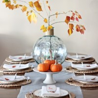 Lovely, simple Thanksgiving tablescape: a grand table and a side table with fall foliage centerpieces, simple neutral china settings, and a few pumpkins | maisondepax.com