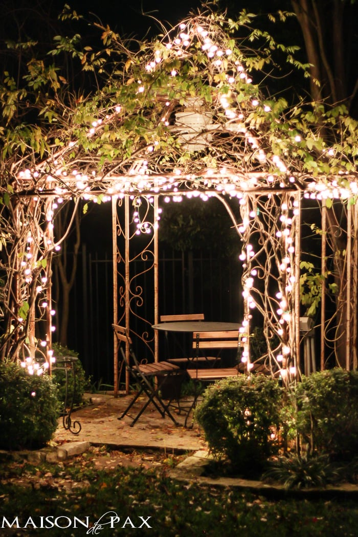 arbor with Christmas lights and a bistro table and chairs