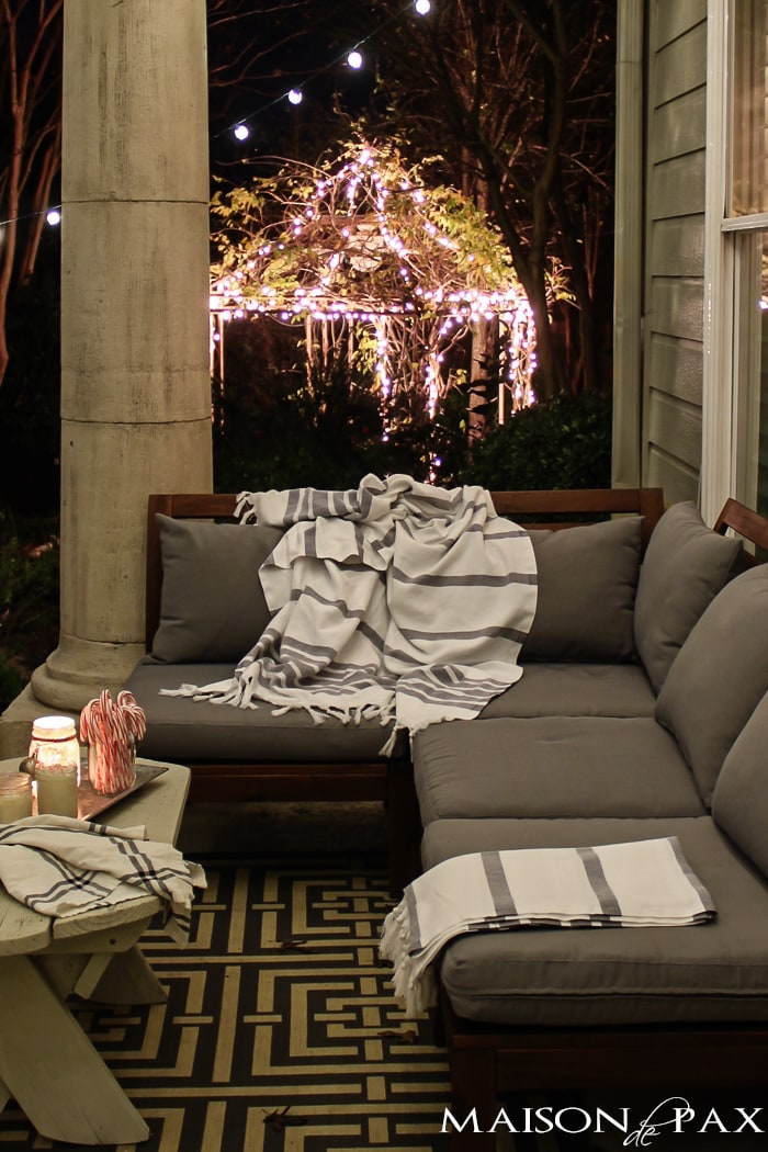 ikea couch with throw blankets, hot chocolate, and white christmas lights