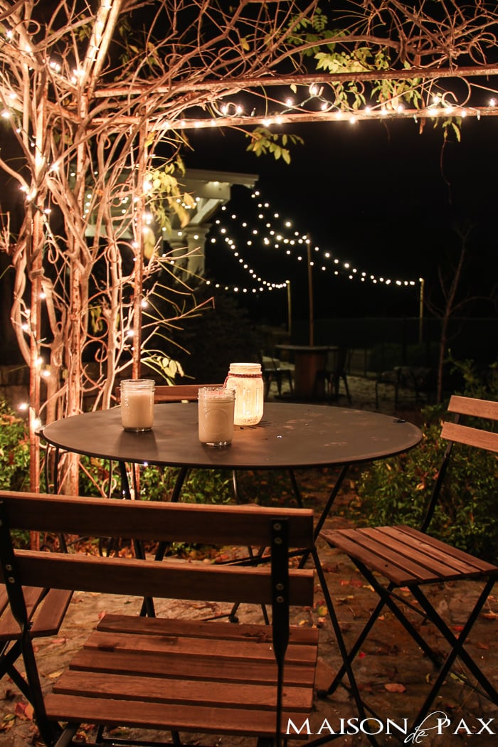 perfectly charming hot chocolate table under an arbor with christmas lights