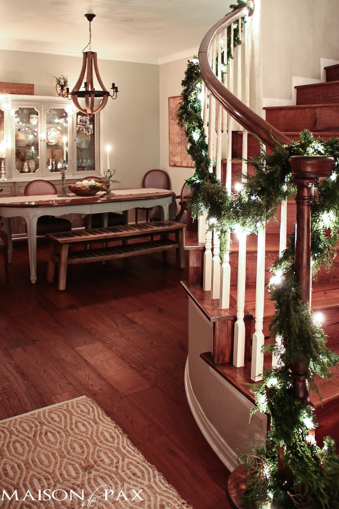 holiday decorating: Christmas table with reindeer candlesticks, string lights on china cabinet, lighted garland on stairs