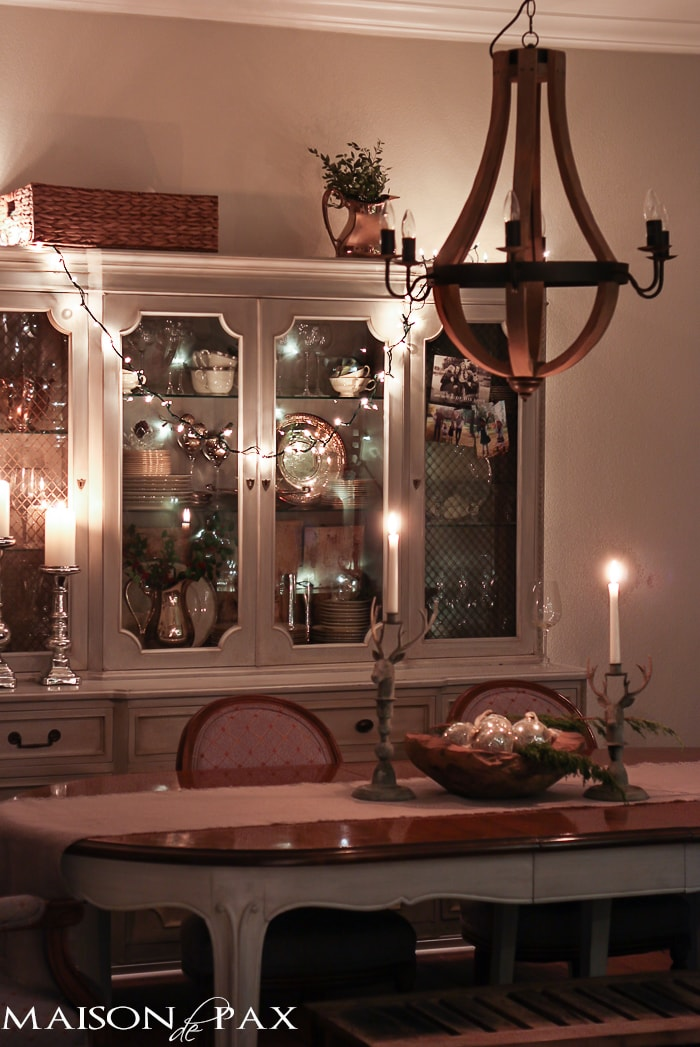 holiday decorating: Christmas table with reindeer candlesticks, string lights on china cabinet