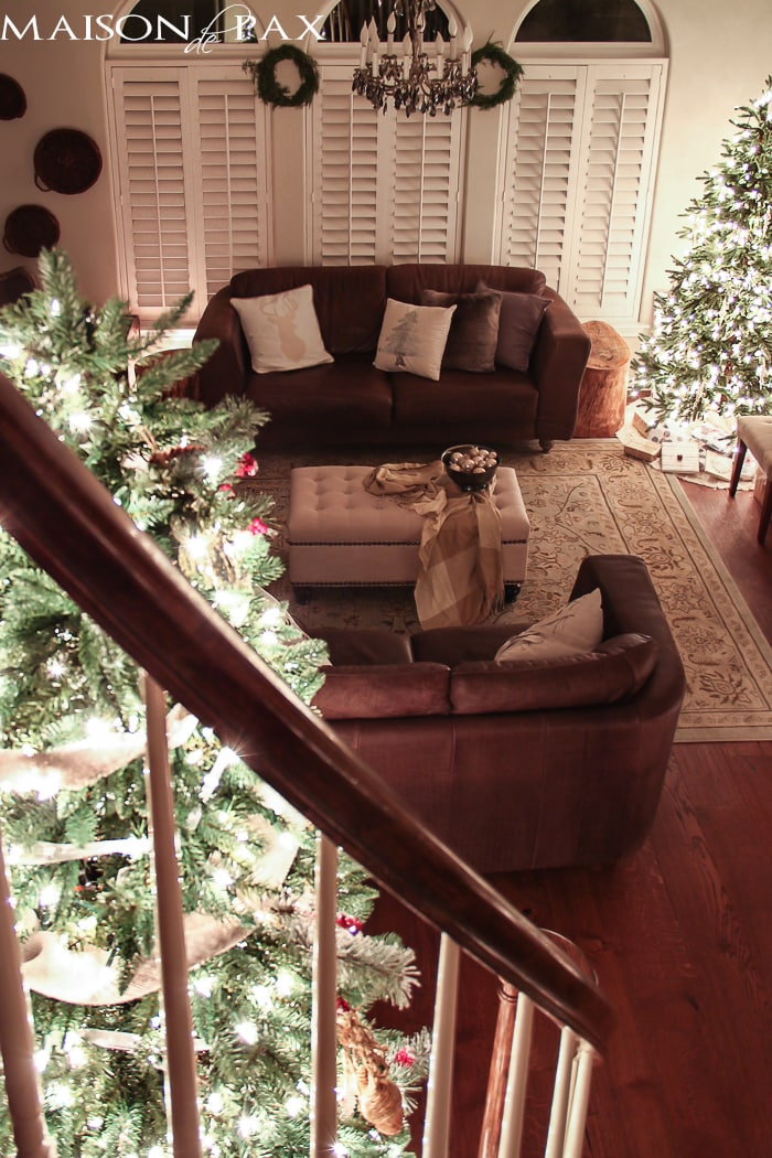 large Christmas tree in stair curve and smaller tree in living room