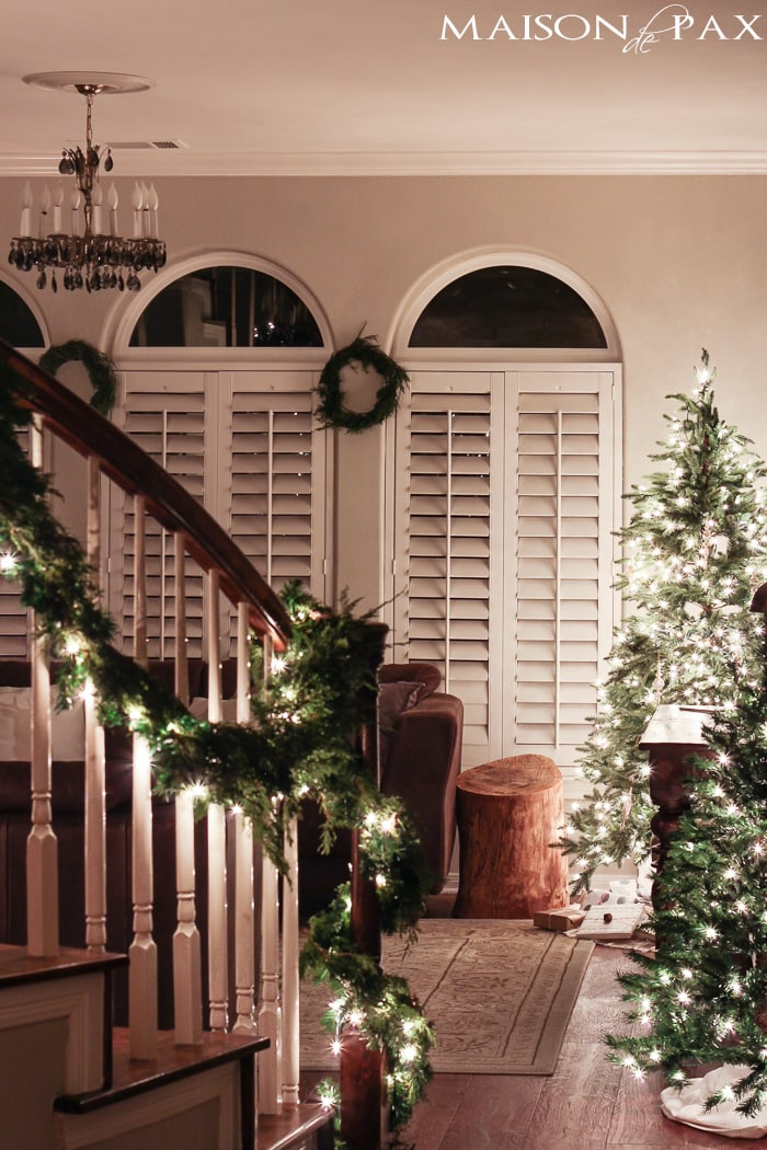holiday decorating: christmas tree with white lights, mini tree, wreaths, lighted garland on stairs