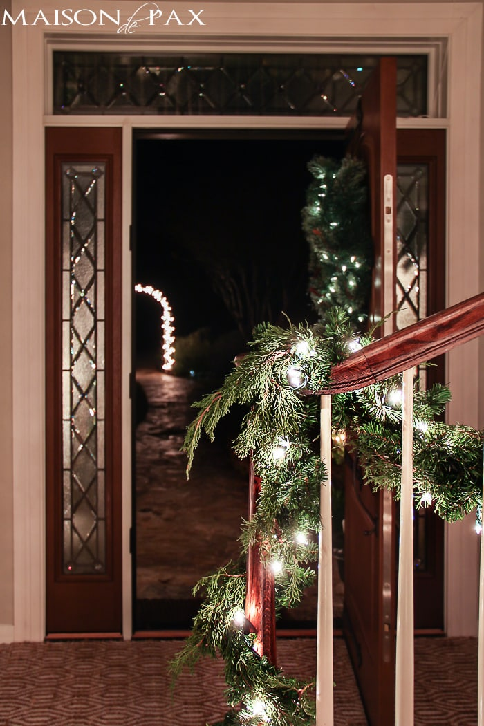 lighted garland and a lighted archway make this holiday entryway simply beautiful