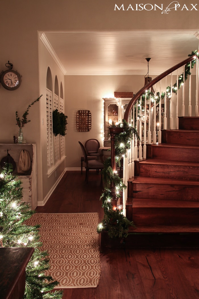 holiday decorating: mini Christmas tree, lighted garland on stairs, string lights on china cabinet