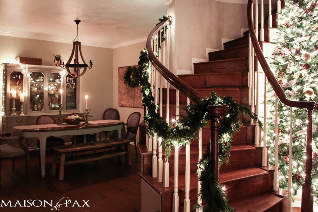 lighted garland on stairs, big christmas tree with white lights
