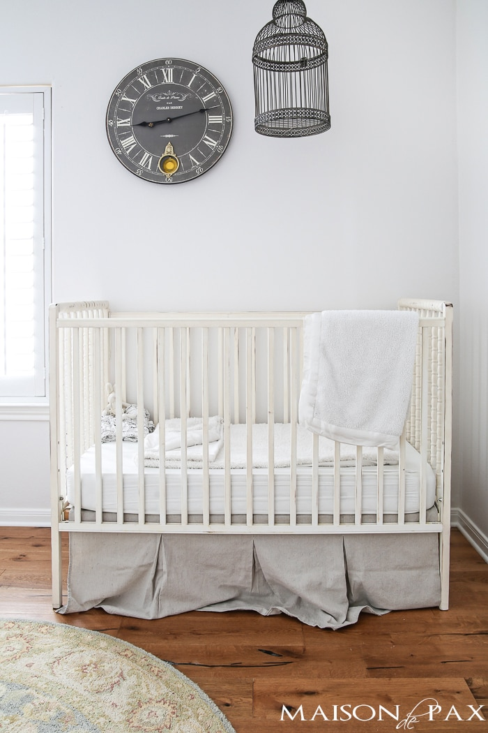 antique white spindle crib with large gray clock and birdcage hanging above - neutral, romantic, and lovely!