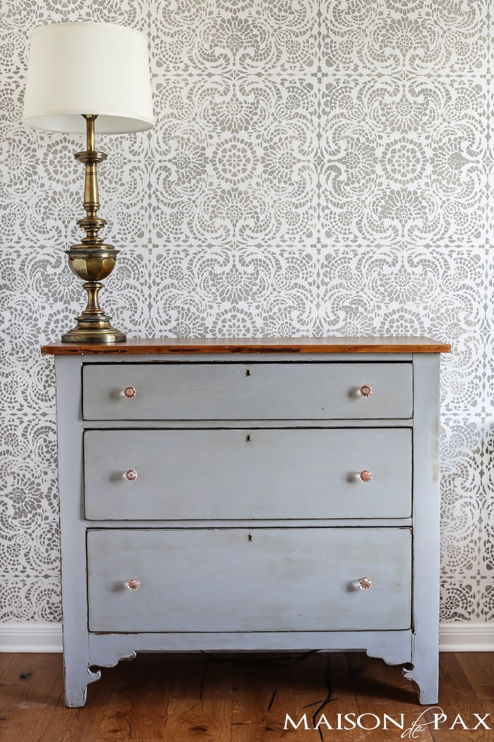 gray painted dresser with pink glass knobs and large, vintage brass lamp are perfect in front of this gray and white accent wall