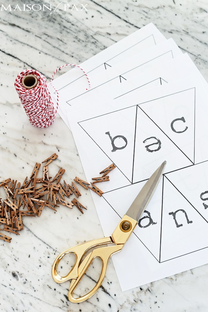 make a Valentine's day bunting from computer paper, baker's twine, and mini clothespins