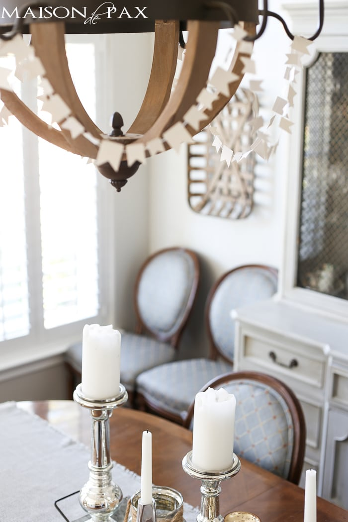 sewn white paper flags draped around a wine barrel chandelier for a festive look