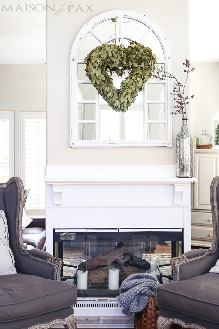 heart shaped bay leaf wreath over window style mirror above mantel - love all the white