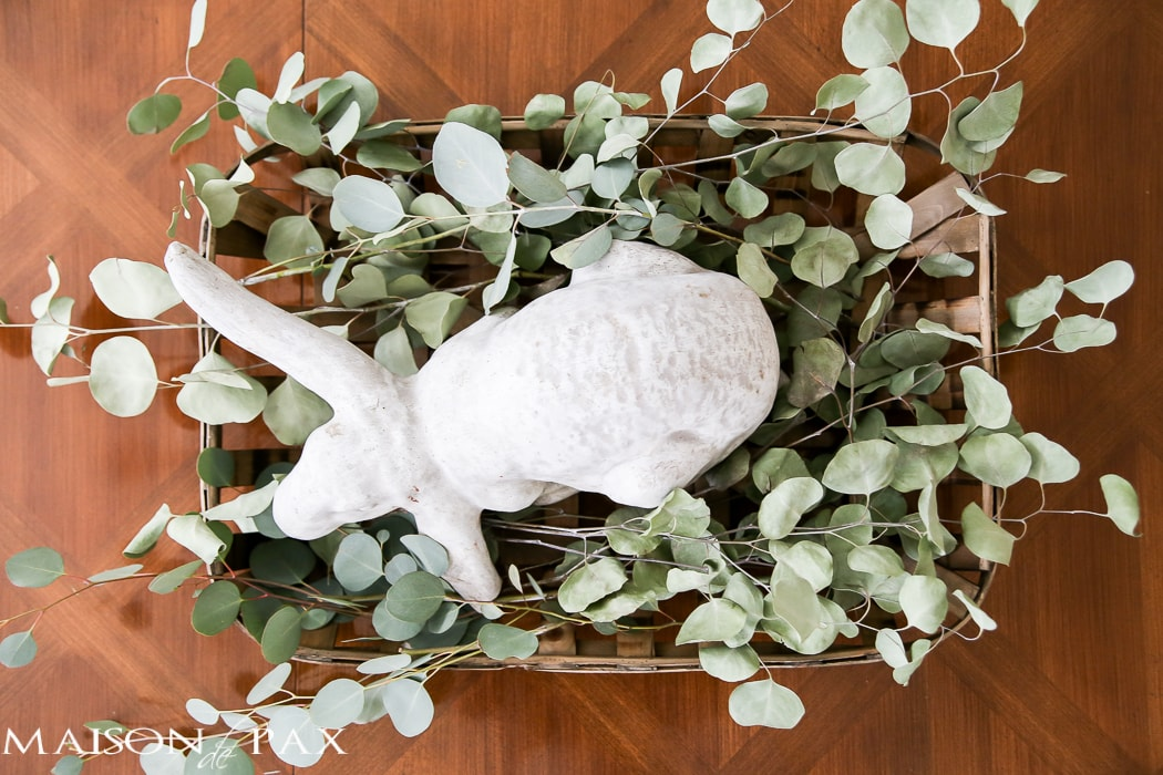 What a cute, simple idea for Easter decor! Use a garden statue bunny in a basket with dried greens as a centerpiece for your table | maisondepax.com