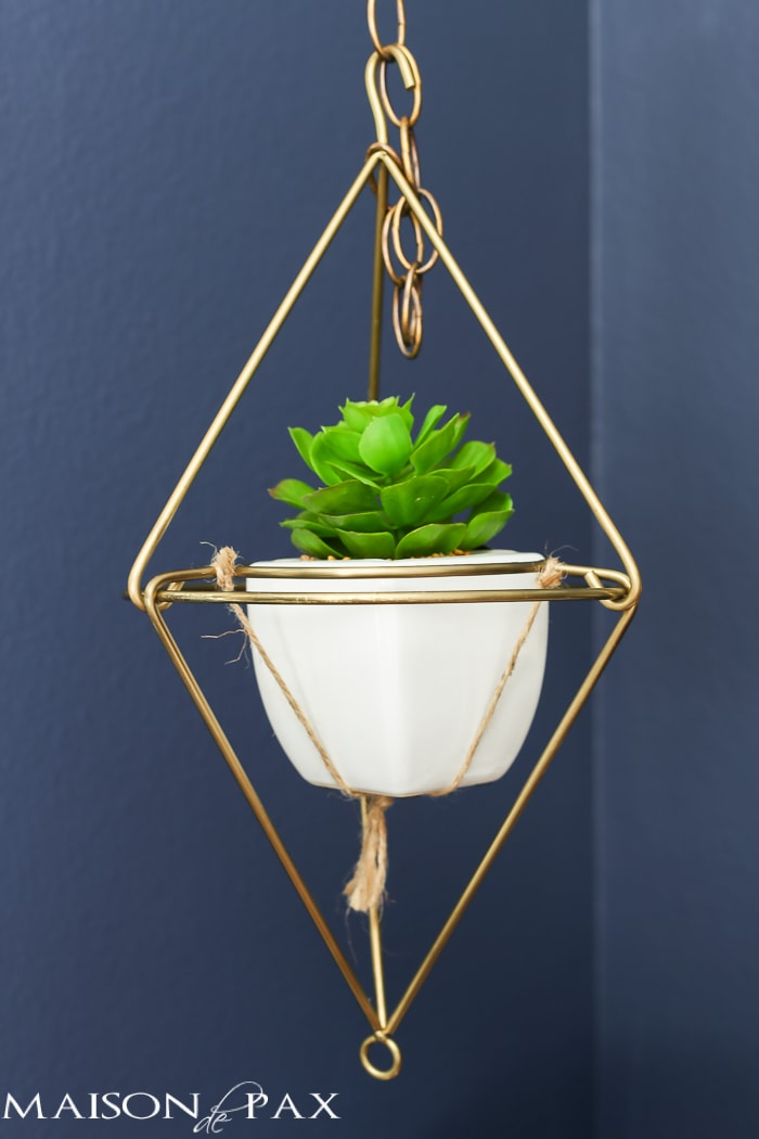 very cool modern, angular hanging plant holder in brass with a white pot and succulent