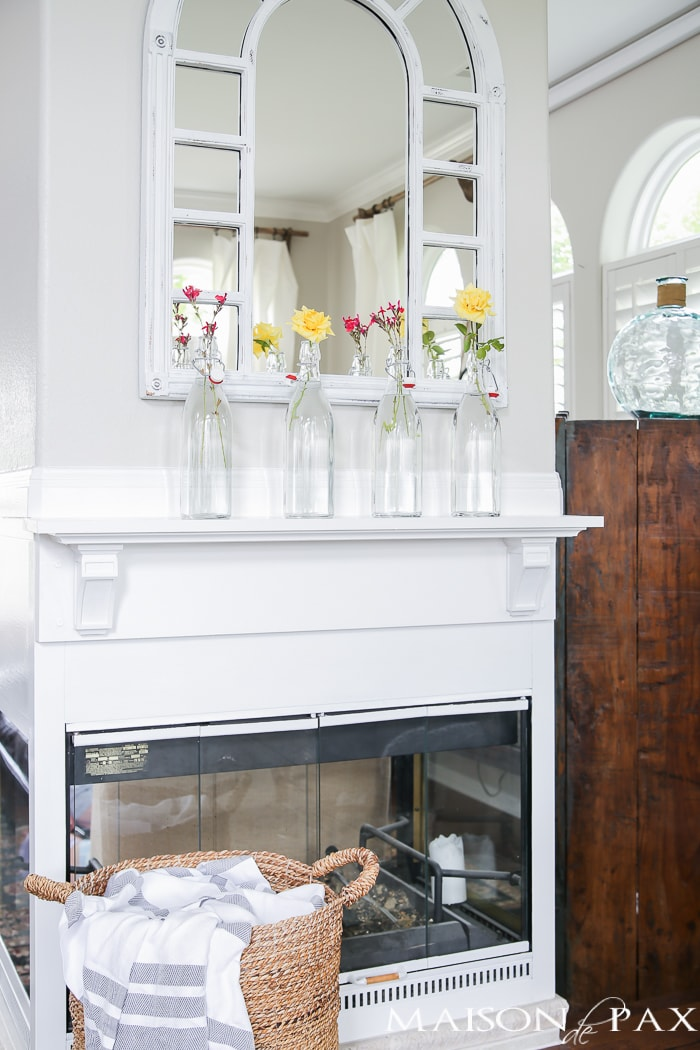simple glass bottles with clipped flowers on the mantel   quick summer decorating ideas