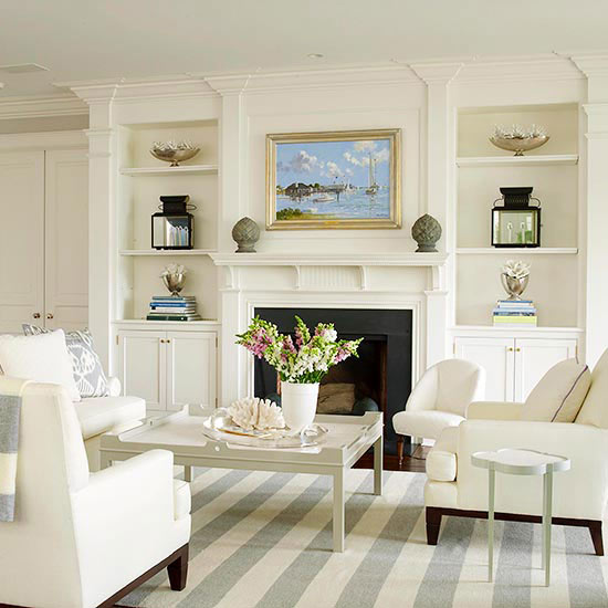 fireplace with white mantel, moldings, and built in bookcases