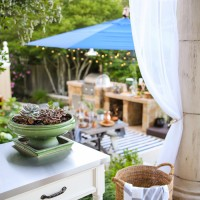 Outdoor Decorating Tips: outdoor curtains and soft twinkling lights bring instant ambiance to an outdoor dining or entertaining space