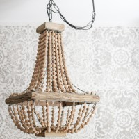 How to hang a plug in chandelier: gorgeous wood bead chandelier in front of a stenciled accent wall