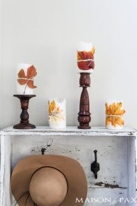 cute fall craft idea: wrap pillar candles in fall leaves and twine