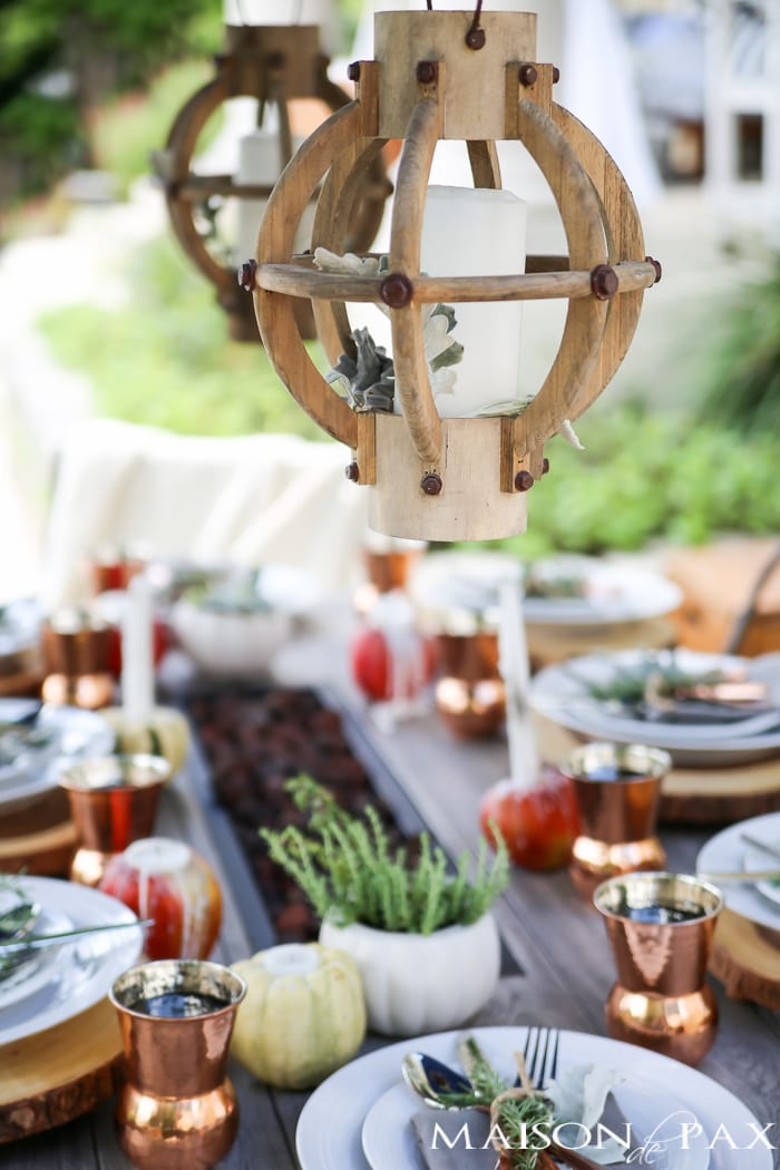 outdoor fall tablescape: lanterns, string lights, apple candles, and other cozy outdoor fall decorating ideas!
