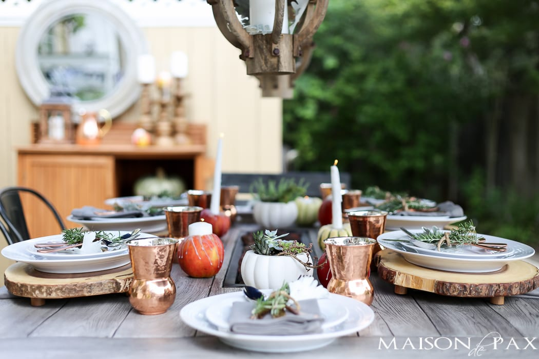 10 tips for a magical outdoor dining table: lanterns, string lights, apple candles, and other cozy outdoor fall decorating ideas!