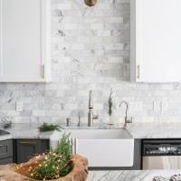 Gorgeous two-tone kitchen design with white upper cabinets, gray lower cabinets, carrara marble counters and marble subway tile backsplash, a farm sink, and a beautiful wood island and brass hardware...